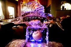 Sailfish ice sculpture atop a pedestal with a large shell frozen inside.  #icesculptures