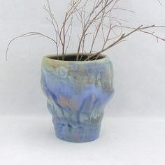 Beautiful blue vase with a twisted and oblong shape. Multi pastel shades of many colours. Can be used as vase, pencil holder or a utensil holder. It is 14cm high.