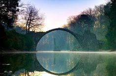 """Diese so düster aussehende Brücke ist alles andere als Fantasy. Inoffiziell wird sie """"Teufelsbrücke"""" genannt. Offiziell heißt sie """"Rakotzbrücke"""" und steht seit 1860 im Rhododendronpark Kromlau in Sachsen."""