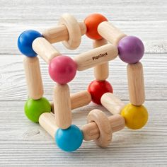 Shop Square Clutching Baby Toy.  Square Clutching Toy comes with two wooden rings that create sound when rattled, which enhances fine motor skills while child grasps and rattles.
