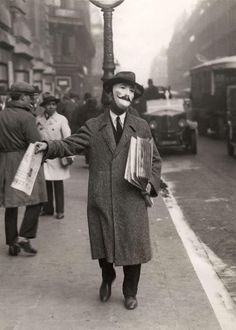 "nedhepburn:   ""Vendeur de journaux"" by Het Leven.Paris, France 1929.   A man selling newspapers in France…not sure what the purpose in the mask is."