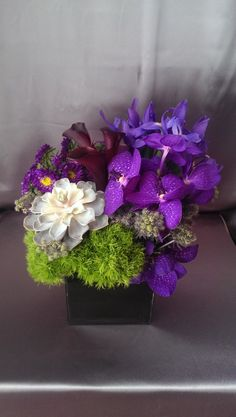 Beautiful purple blooms of vanda orchids, Iris, thistle, trick, matsamoto, calla lilies, & succulent in a black square container, to blow mom away this Mother's Day!