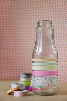 Decorando  botellas con cinta adesiva de colores.