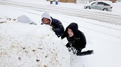 Karen, Robert and Darren Jones build a giant snowball in their front yard on Catalina Drive Thursday morning. (Photo by Rob Ostermaier / Daily Press)