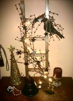 LiL prim ladder that the hubby made. I painted it, added some Prim pip garland, painted some little wooden stars black, added them into the mix, made a crow and attached it, then added some LED lights.