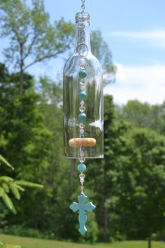 Wine Bottle Wind Chime Turquoise Cross Wind by WhiteRoosterShoppe wine bottle crafts Items similar to Wine Bottle Wind Chime, Turquoise Cross Wind Chime, Recycled Wine Bottle Chime on Etsy Wine Bottle Chimes, Wine Bottle Garden, Wine Bottle Trees, Glass Wind Chimes, Diy Wind Chimes, Wine Bottle Art, Cutting Wine Bottles, Empty Wine Bottles, Wine Bottle Candles