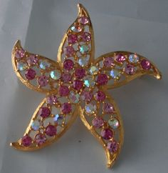 """Starfish Goldtone Crystal Pin Signed Lee Angel. Aurora borealis and sparkly pink faceted crystals set in gold tone starfish backing. Back signed Lee Angel (New York). Measures about 2.5"""" around."""
