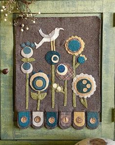 "1894 Cottonwood House: #276 ""Ring A Round the Posies"" Wool Appliqué Pattern  The basis of this Simple, Sweet design is the unique combination of five different sizes of circles to create a Lovely Garden of Posies. The Wool Tabs at the bottom spell out POSIES on Vintage Tags! Thus ""Ring A Round the Posies""!  Inspired by our ""Ring A Round Posies"" Wool Bundle!  Finished size: 16"" X 21""  This design also looks AMAZING in Autumn Hues, with AUTUMN on the bottom tabs!!"