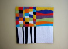 """Rumyana Lafchieva, 50/50: """"I was inspired by (the variety of life). Each quarter has a different message. The black and white quarter shows the serious side of life so the lines are straight. The colored wavy stripes express the joy of life. The colored blocks meet and mix in a real life with different emotions, happy or bad moments like a puzzle. The last quarter is white. It could be the past with no memories or the future with many expectations. I used the white as balance to a whole…"""
