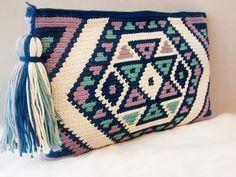 Bolso de mano en crochet, de estilo wayuu. Con forro interior y bolsillo. Hecho con algodón 100% en azul, crudo, lila y verde. Tamaño aproximado 28x18 cm  Se pueden realizar pedido personalizando el color, tamaño. El tiempo de ejecución es de 1 semana y de 1 a 3 días para el envío.  Envíos a España, para envió a otros países consultar por e-mail.