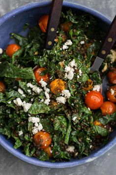 A lovely summer tomato salad featuring softened kale tossed with burst tomatoes, za'atar, black lentils, and an easy lemon vinaigrette for dressing.