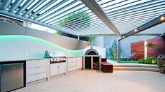 Pergola covered outdoor kitchen with aluminium framed white doors in Australia by Alby Turner & Son