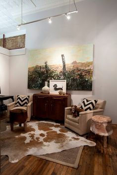 ... Contemporary Home With The Wooden Sideboard, Cream Colored Sofa Chairs,  And The Cowhide Rug And Stools. Home Designed By Aiken Interior Design  Firm, ...