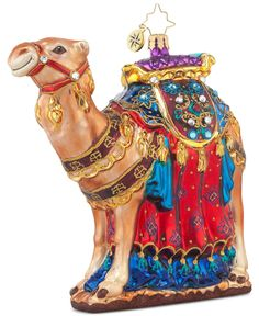 This From the Far East ornament from Christopher Radko features a camel with an elegantly decorated red, blue, and purple saddle. This ornament is a beautiful gift or addition to your tree. | Glass |