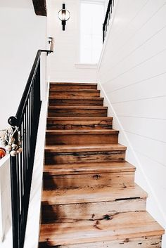 Gorgeous natural wood stairs, black hand rail, white shiplap stairway. I love this!
