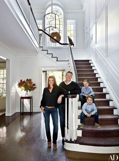 The couple and their two sons, Chase (top) and Lance, in the entrance hall; the light fixture is by the Urban Electric Co | archdigest.com