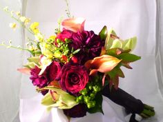 Enchanted Florist Las Vegas-fall inspired bouquet made of red roses, green and yellow orchids and mango callas.