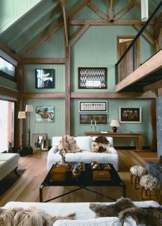 Great chalet interior with the green contrasting with the wood timber. Great sheepskins on the sofas too!