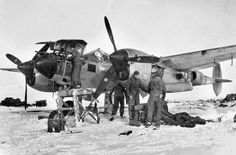 Ground crewmen use an external heater to warm up one of the twin engines aboard a Lockheed P-38 Lightning fighter of the Ninth Tactical Air Force