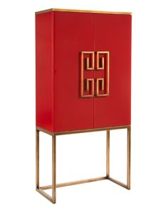 This dramatic red cabinet on stand has antique gold stylized Greek Key handles and matching trim. The cabinet is painted gold inside with adjustable shelves. The door fronts are reverse painted glass