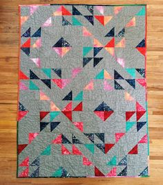 This quilt is made from various batik fabrics and essex linen. The free motion quilting was inspired by Matisses cutout series. The pattern is a version of Suzy Quilts Indian Summer.  50 x 67.5 100% cotton Machine wash cold/warm; tumble dry low Handmade in Santa Fe, New Mexico