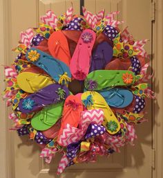 Flip Flop Wreath with 12 flip flops, chevron ribbon, polka dot ribbon, rhinestones with flowers, curly bows and more.  Measures about 30 inches wide.  Colors ma