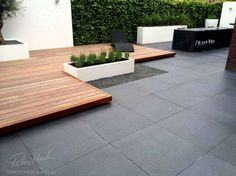 Warm decking floating over dark tiles