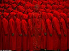 Camouflage: The artist blends in with rows and rows of people dressed in red hoods    Liu Bolin