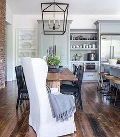 Isn't this a wonderful farmhouse kitchen! I'm particularly partial to wing chair on the end. Found via @lavenderhillinteriors