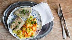 Gedünstete Forellenfilet mit Möhren und Kartoffeln auf einem Teller