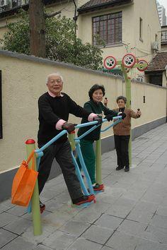 "Elderly people stay healthy through publicly offered work out ""adult playgrounds""."