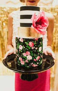 This cake was made for a NYE  cocktail party. Custom printed edible image was used to create  the bottom tier pattern, edible gold leaf, fondant and a Wafer Paper Fuchsia flower