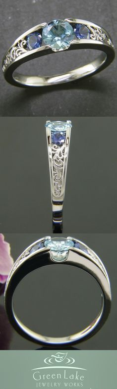 This sparkling white gold mounting holds an aquamarine neighbored by sapphires. Ornate filigree curl panels are featured in the opening of the shoulders #GreenLakeJewelry #Ido #EngagementRing
