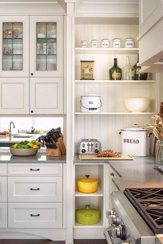 To give this kitchen a farmhouse style, the designer used a combination of cabinets and open shelves with beadboard on the back and vintage enamelware.