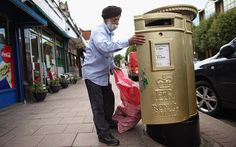 A postman empties a gold post box in Isleworth on August 6, 2012 in London, England. The post box was painted gold to celebrate British athlete Mo Farah's victory in the Men's 10,000m race at the London 2012 Olympic Games