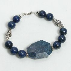 "Handmade gemstone lapis bracelet features a strand of round semi-precious lapis gemstone with large faceted slice, silver beads, wire band, and lobster claw clasp. 8"" in length. Add a necklace, pendan"