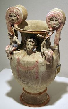 Canosan polichrome pottery volute krater, Apulia, early 3rd century B.C.  The obverse with a hanging pink fillet, the neck centered by a molded frontal head of Dionysos, wearing an elaborate pink, white and blue fillet of ivy and berries, the ties painted along the shoulders, framed by two winged Erotes seated on square platforms along the shoulders, each wearing a pink mantle folded over to blue at the waist, the volutes with female mascaroons, 39.4 cm high. Private collection