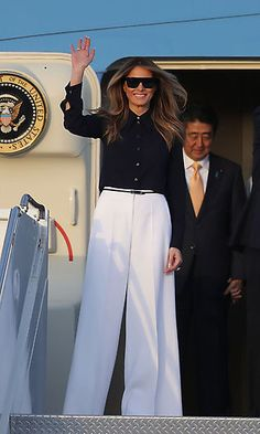 First Lady Melania Trump disembarked Air Force One with Japanese Prime Minister Shinzo Abe at the Palm Beach International Airport wearing high-waisted, white wide-legged Michael Kors pants paired with a black button-front blouse. Photo: Joe Raedle/Getty Images