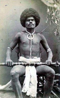 Fijian mountain warrior, Kai Colo, holding a rootstock club and wears a boar's tusk necklace, The African presence is world wide. We Are The World, People Around The World, In This World, Kings & Queens, Anthropologie, African Diaspora, Portraits, African American History, World History
