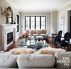 living room, parisian chic, plinth, topiary, english sofa, sheepskin pillows, zebra print pillows, glass coffee table, black arm chairs, walnut floors, black windows
