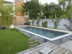 Semi-inground rectangular pool surrounded by concrete, stone or marble.