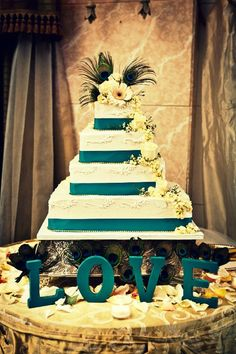 "peacock themed wedding cake, do not like the peacock.. but like the teal ""stripes"" on the white."