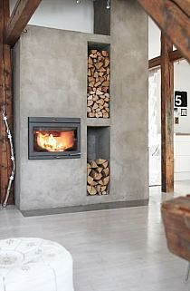 love this contemporary fireplace with the niches for the stacked wood. the neutral grey plaster against the warmth of the wood beams and posts adds a nice contrast.