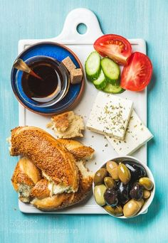 Turkish traditional breakfast with feta cheese vegetables olives simit bagel and tea