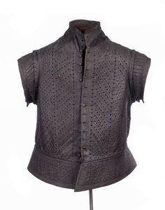 A youth's dark brown leather jerkin, decorated with vertical and diagonal scored bands, and diamond, heart and star pinking. The jerkin is fastened with decorative pewter buttons which imitate those fashioned from worked silk or gilt thread over a wooden core. Traces of silk stitching on the front suggest that the garment may have been lined during the 19th century.     Date  1555 AD - 1560 AD