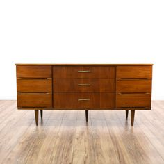 This mid century modern dresser is featured in a solid wood with a glossy warm walnut finish. This long dresser has 9 spacious drawers, tapered feet and carved inset handles. Stunning and stylish storage piece perfect as a bar buffet! #midcenturymodern #dressers #longdresser #sandiegovintage #vintagefurniture