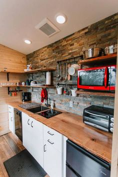 The kitchen includes an induction burner, dishwasher, under counter refrigerator, microwave, and toaster oven.  Live edge countertops and slate tile give the home a rustic cabin feel.
