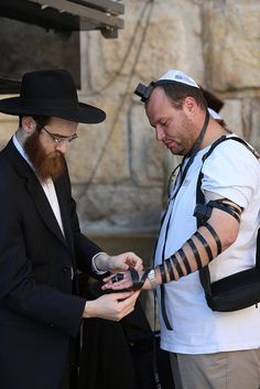 An Orthodox Jew helps a visitor to wrap tefillin around his arms. They are a set of small black leather boxes containing scrolls of parchment inscribed with verses from the Torah, which are worn by Jews during weekday morning prayers