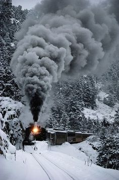 Vertical photograph of the front of an old-fashioned steam train, moving through the snow covered hillside of the San Juan Mountains in Colorado. The Durango & Silverton Narrow Gauge Railroad train chugs through the snow, San Juan Mountains, Colorado Wall Art is from National Geographic and is by Paul Chesley. Discover more train photography images at Great BIG Canvas.