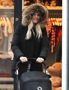 Doting mum: Sienna Miller fur trim winter coat